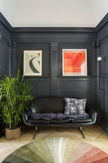 The space is now defined by a contrasting coat of Benjamin Moore Witching Hour. The cozy niche contains a vintage Overman loveseat and Pholc wall sconce.