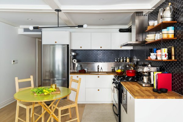In the garden apartment kitchen, IKEA cabinet boxes received fronts from Reform, in the Basis style. An Andrew Neyer Barbell Pendant echoes the black two-inch hex wall tile. The black wire and wood open shelves are the client's own and similar to the String Pocket Shelf, says the firm.