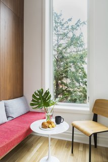 In the quiet eating nook, a custom bench sidles up to a Saarinen Side Table and  Vitra Standard chair by Jean Prouve.