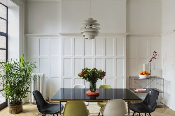 A custom dining table made by the owner is surrounded with vintage Eames chairs and topped with a vintage Louis Poulsen PH Snowball pendant by Poul Henningsen. The metal sideboard is from Muji, and the paneling is original.