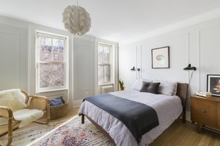 In the master bedroom, a pair of DCW Mantis sconces are positioned between the traditional molding, which mimics what's found on the lower floor. The paint color is Benjamin Moore Alaskan Husky custom mix, and the quilt is from Hay. The side chair is an Urban Outfitters find.