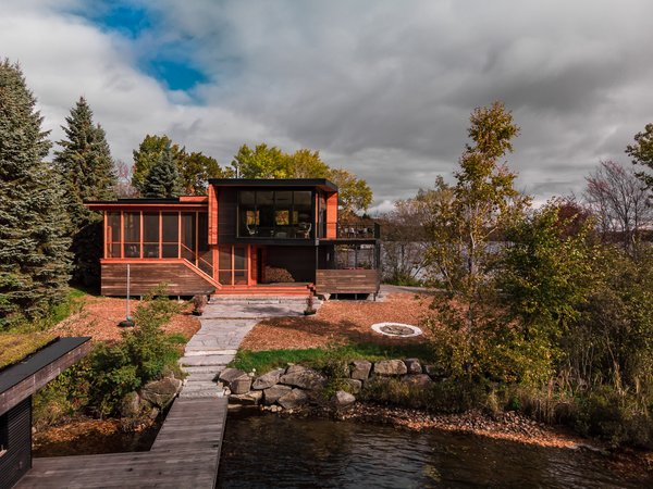The 1,600-square-foot lake home has three bedrooms and two baths, and was built for a family of three. The narrow lot has views of the water on both sides, so the firm placed the living areas on the upper floor to take advantage of this, and positioned a screened-in porch (seen on the left) to mediate between the interior and exterior.