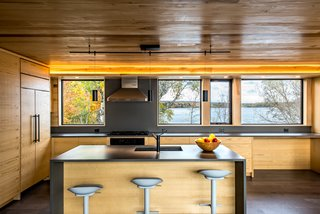 The kitchen windows reveal sightlines to the water on the other side of the home, so the panoramic views afforded by the narrow lot are fully utilized.