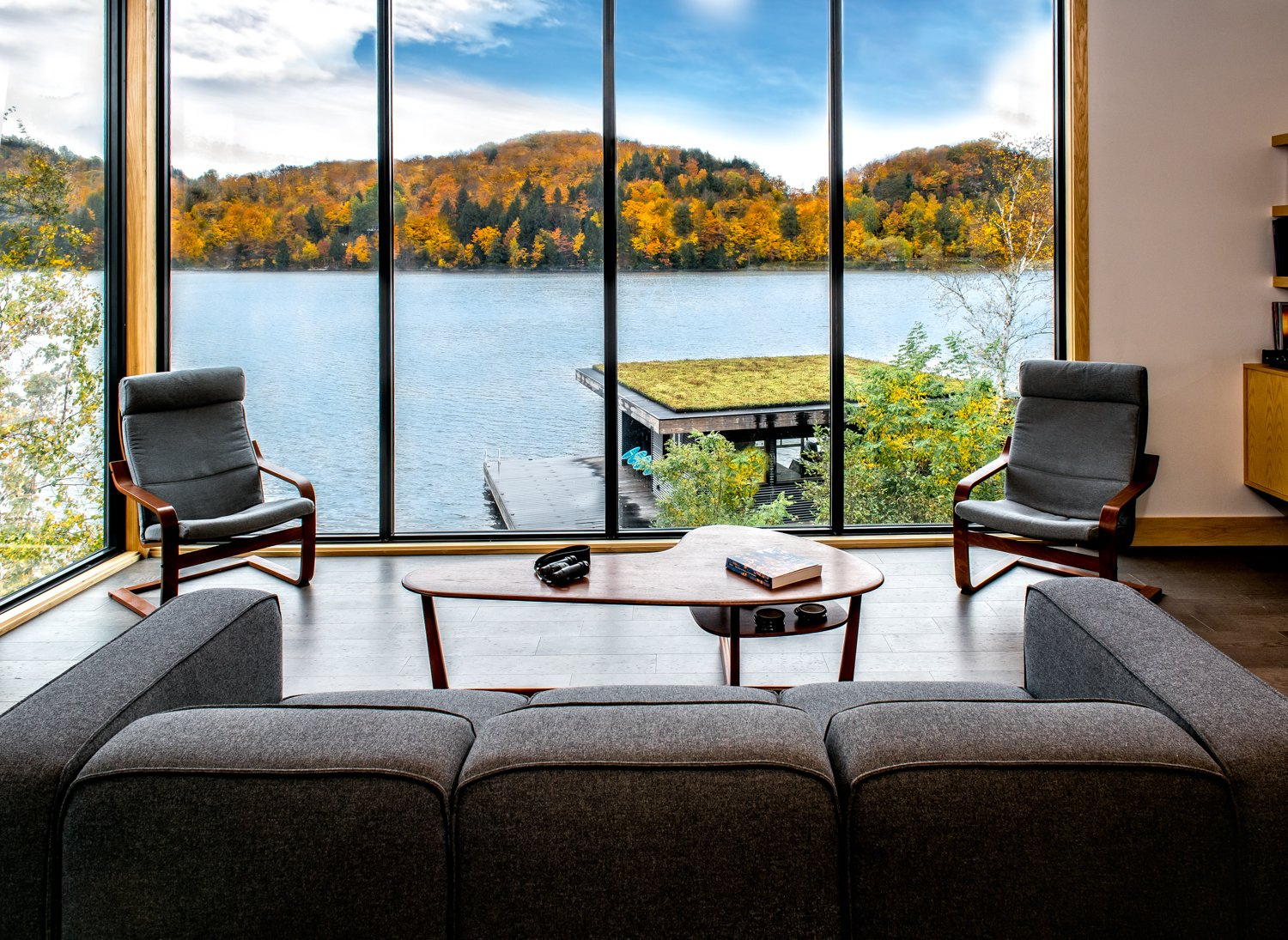 Tall glass windows in the living room frame the view.