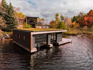 The boathouse has a green roof and corrugated metal siding.