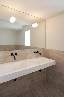 The main bathroom is clad in travertine and maintains the understated color palette found throughout the home.