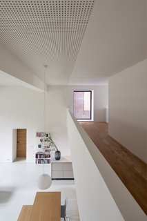 """The view from the mezzanine to the main floor. Sound-absorbing plasterboards on the ceiling modulate the acoustics in the home. """"I also like how we used the sound-absorbing ceiling in this project,"""" says Elklund. """"Next to being very functional for such a space, it adds texture and rhythm in a subtle way."""""""