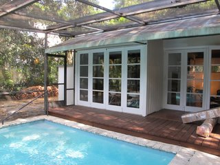 Previously, the rear facade connected to a pool area that ran perpendicular to the house. Several sets of double doors with mullions impeded sightlines outside.
