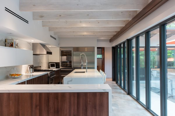 The kitchen and dining areas now occupy the new single-level wing and also overlook the backyard via the glass wall. Silestone countertops waterfall over walnut cabinetry, and exposed wood rafters overhead received a coat of whitewash.
