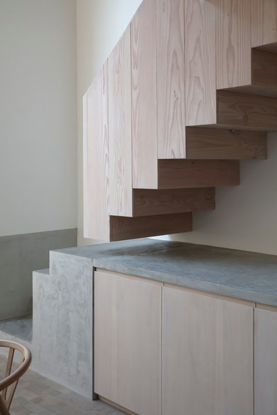 The staircase was moved to the other side of the room and is now a sculptural focal point, thanks to a striking material change from wood to concrete.