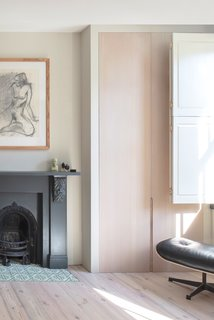 Now, bespoke wardrobes by Grovecourt flank the fireplace, which was newly painted. Hearth tiles are from Bert and May.