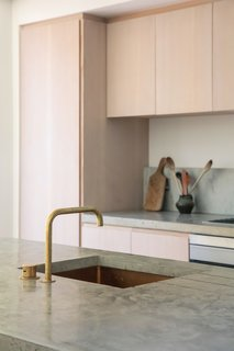 Cast concrete counters overlay a brass sink (the Alveus Monarch Quadrix 50) and are bedecked with a Vola single mixer lever in natural brass.
