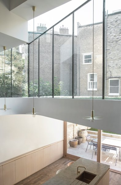 The firm specified an opening at the first floor, to connect it with the new kitchen and dining room below. The reconfigured glass extension allows light and views deeper into the narrow house.