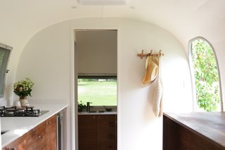 A view down the aisle to the bathroom, with the kitchen on the left and the eat/work counter on the right. The Modern Caravan combined walnut cabinetry and red oak flooring, with white counters, tile, and walls.