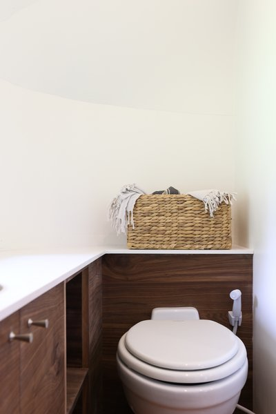 The walnut wraps the bathroom, offering plenty of storage, and continuity with the rest of the small trailer.