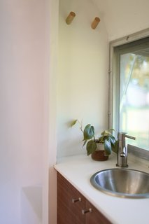 The bathroom has a stainless-steel sink and faucet, Hanex solid surface countertops, and Schoolhouse Electric pulls.