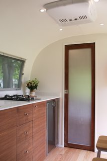 The bathroom pocket door, a Modern Caravan signature, is opaque plexiglass framed in walnut.