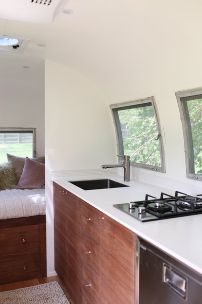 The kitchen is seven feet long and 10 inches deep. Hanex solid surface countertops with a thin profile sit on top of custom walnut cabinetry with Schoolhouse Electric pulls. The stainless-steel sink is a 20-inch-wide model by Kraus with a Grohe faucet.