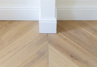 Engineered oak floor boards from Chauncey Timber were laid over the existing floors in a chevron pattern. The meeting line denotes where the wall between the two rooms was removed.