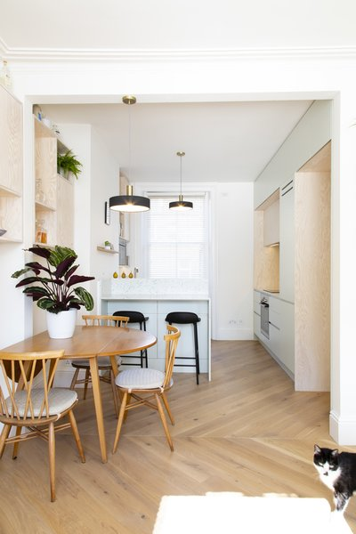 Opening up the doorway made space for a designated dining area, which has a vintage Ercol table and chairs. Ferm Living Socket Pendants hang in the kitchen and over the table.
