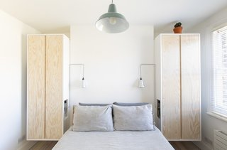 In the small bedroom, just 107 square feet, Baulier designed wall-hanging storage cupboards that can double as bedside tables thanks to cut-out niches.