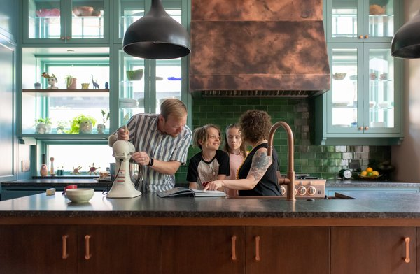 """The Nickell family, including children Dash and Arli, makes cookies in their new kitchen. """"Both Shondi and Jake, being a part of Threadless, have such creative backgrounds themselves,"""" says Suzanne. """"The best part was just how seamless and easy it was to work through the colors and the palette and the materials."""""""