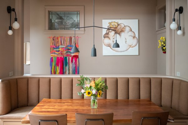 "The Shumakers opened up the wall to the stairwell behind the banquette, which makes space to display the family's art collection and spread light around. Shondi and Jake ""fell in love with a Farrow & Ball color called Dead Salmon, which is a really pretty flat pink, so it became more of the neutral in the space,"" says Suzanne."