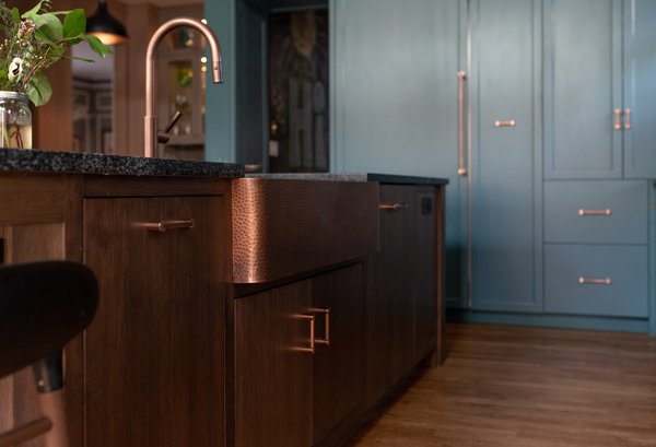 A hammered copper farmhouse sink from Sinkology and copper hardware from Decorator Hardware contrast warmth against the blue and green tones of the cabinetry. The existing wood flooring was kept, just sanded and stained to match other areas of the house.