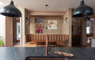 "Now, a ten-foot long banquette fronted with a West Elm table anchors the eating alcove across from the island, and beckons visitors to have a sit. The family hosts everything from holiday get-togethers, to school and company functions in their new space. ""We wanted to make everybody feel welcome,"" says Shondi."