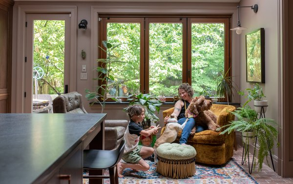 "Shondi and Dash enjoy the new sun room space, which now provides the perfect spot for morning coffee, as well as a home for Shondi's plants. The sun room is ""the connection to the outside,"" says Suzanne. ""We changed the materials on the floor from wood to Chicago common brick, so it feels a little more exterior. It also has a heated floor underneath so it's warm in the winter and also absorbs light during the day, which keeps the floor warm."""