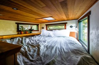 The bed loft in the El Toro can accommodate a California king mattress and is surrounded by windows trimmed in reclaimed, vertical grain, clear heart redwood.