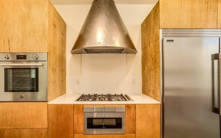 The steel hood vent design was custom-made and inspired by a steel circular fireplace in the Frey I home.