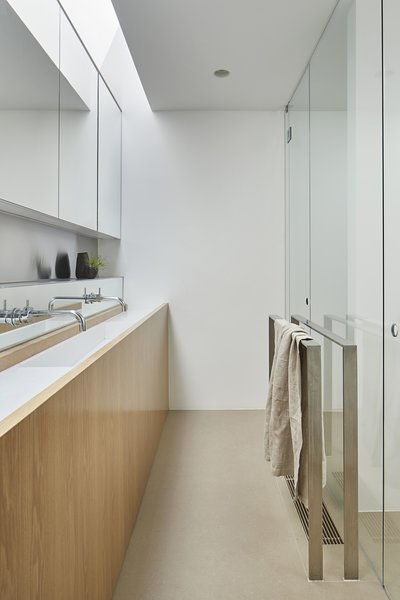 """Once you use the pivot doors to enter these wet areas, spaces are lit from above and the center of the pod is white,"" says the firm. ""Large sheet tiles that match the timber floor in tone are used for the wet area floors, and similar large format tiles in white are used for the majority of wet area walls."" The vanity is fashioned from American oak, while the counter and custom sink are composed of white HI-MACS solid surface material."