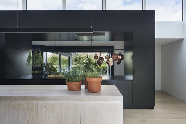 A hallway behind the kitchen received a 4-meter-long plate glass window (or about 13 feet) in order to lighten up a dark spot in the plan and visually connect to a new courtyard garden.