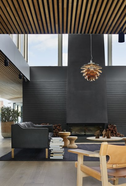 "Now, a custom, steel-clad fireplace chimney stretches over 4.5 meters tall and imparts a sense of hygge. It was ""designed as a contemporary take on the pressed copper flues typical of the era, while complementing and increasing the effect of the existing raked ceilings to the space,"" says the firm."