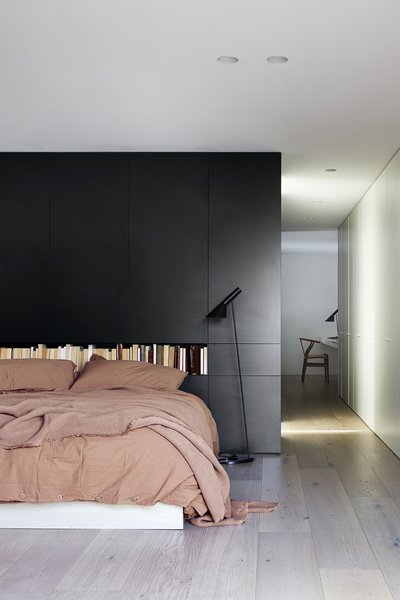 "The firm relocated the master bedroom to foster privacy, and it is joined by an en-suite bathroom and private study, seen down the hallway. ""Black Laminate was used as the finish for the wall paneling, and provided concealed storage behind the master bed,"" says the firm. ""This black laminate continues around all exterior surfaces of the master en-suite, powder room, and study joinery, to form a 'black pod' of sorts."""