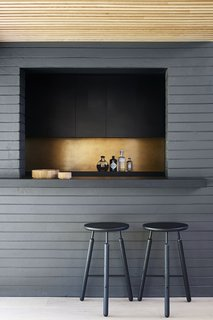 The backsplash is a tarnished sheet of bronze. Raft Stools by Norm Architects provide understated seating.
