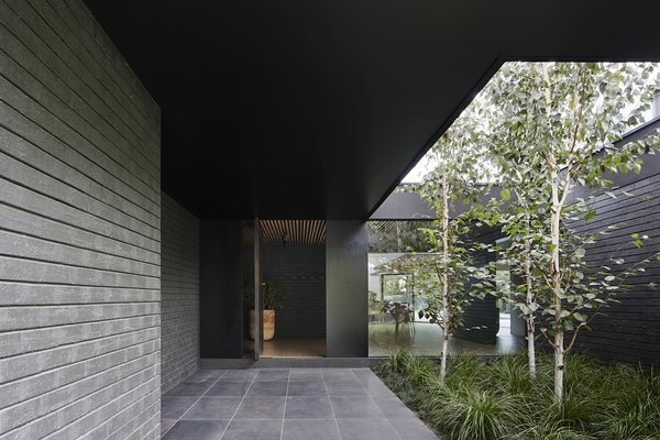 A honed basalt walkway leads to the re-imagined front door.