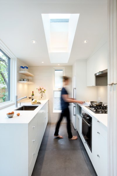 In the kitchen, white Caesarstone counters seamlessly top white flat-front cabinets.