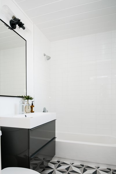 """We updated each of the guest bedrooms and full guest bathroom with whimsical tile and statement finishes,"" says the firm. The designers used a graphic patterned Merola tile on the floor, pairing it with a black vanity from IKEA and a CB2 Infinity Mirror. The light fixture is the Trent Austin Alguno 2-Light Vanity Light."