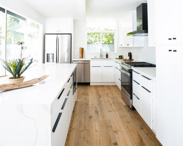"""We designed a fully-custom, expanded chef's kitchen featuring European-style cabinets, a large island with waterfall countertops, and hardwood floors,"" say Sommer and Costello. The light and bright kitchen has cabinetry by Gilbert Sojo, quartz counters, and a streamlined black GE range hood that syncs with the black finger pulls from Cosmas."