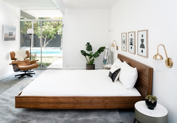 Two West Elm Pelle Sconces flank the Brayden Studio Horsham Platform Bed, while the sliding doors now reveal views to the restored backyard.