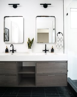Sommer and Costello combined Derengge Two-Handle Faucets in matte black with the Lucent Light Shop Vortice Sconce over CB2 mirrors.
