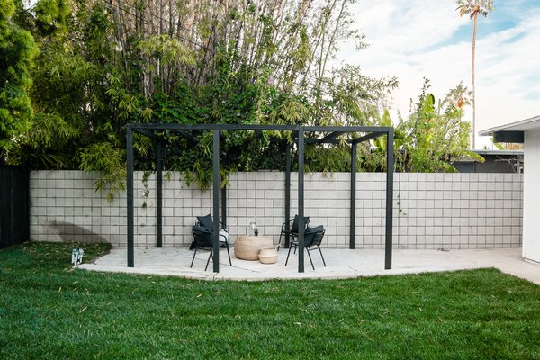 Now a painted wood pergola frames an intentional seating area.
