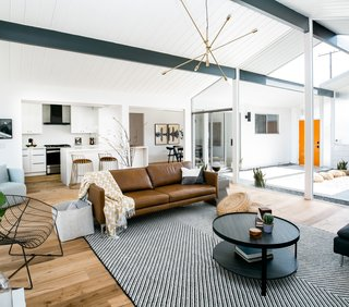 """""""Our team selected furniture and décor that would give the home a modern, midcentury vibe while still feeling invitingly livable and current,"""" says the firm. The couch is the Echo Sofa from Article."""