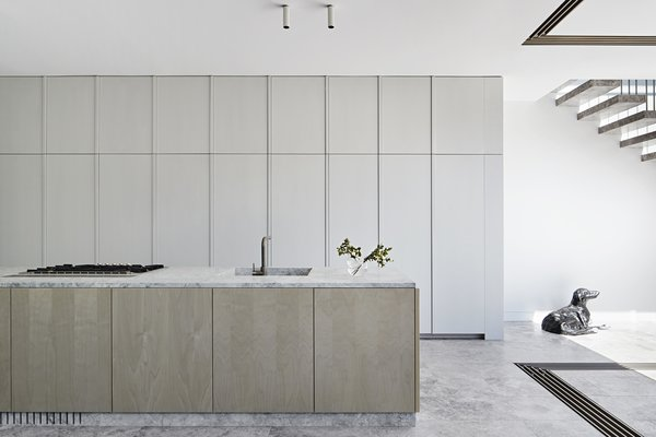 In the kitchen, custom cabinetry conceals a plethora of appliances for a streamlined look, including two integrated Liebherr refrigerators, one integrated freezer, one Eurocave wine cabinet, and two Blum Space Towers. The island is faced with gray birch veneer, and the sculpture is by Jeff Thomson.