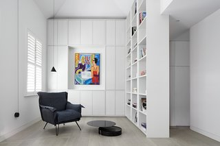 The library provides sleek, closed storage and open shelves that reach over 12 feet high. A Moroso/Diesel Cloudscape Chair sits beside the De La Espada Laurel Coffee Table, with a Flos String Light strung overhead. The painting is by Krzysztof Kokoryn.