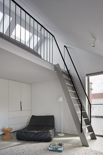 A cozy hang-out space in a second-floor bedroom in the stables is created by a mezzanine floor.