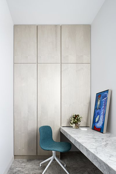 In a private study, a thick built-in counter desk composed of marble and Savior Blue limestone brings texture and color to the neutral scheme, and highlights the artwork.