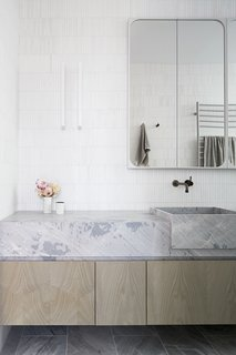 Limestone floor tiles sync with a vanity counter formed in Elba Dolomite, complete with integrated sinks of the same material. Thassos Marble Kit Kat Tiles cover the wall. The mirror is a Robson Rak-designed mirror cabinet painted in Dulux Natural White.